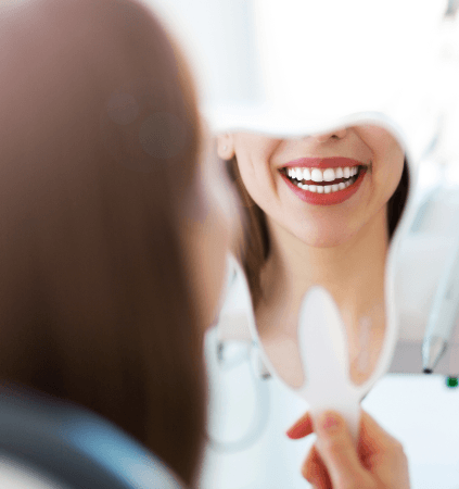 Woman looking at her smile with porcelain veneers
