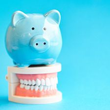 light blue piggy bank sitting on top of a set of false teeth