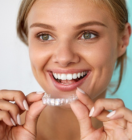 Woman placing Invisalign tray