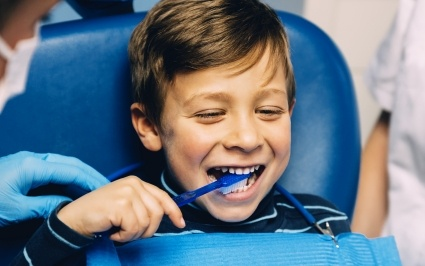 Young boy practice tooth brushing during children's dentistry visit