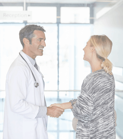 Woman shaking hands with dentist at preventive dentistry visit